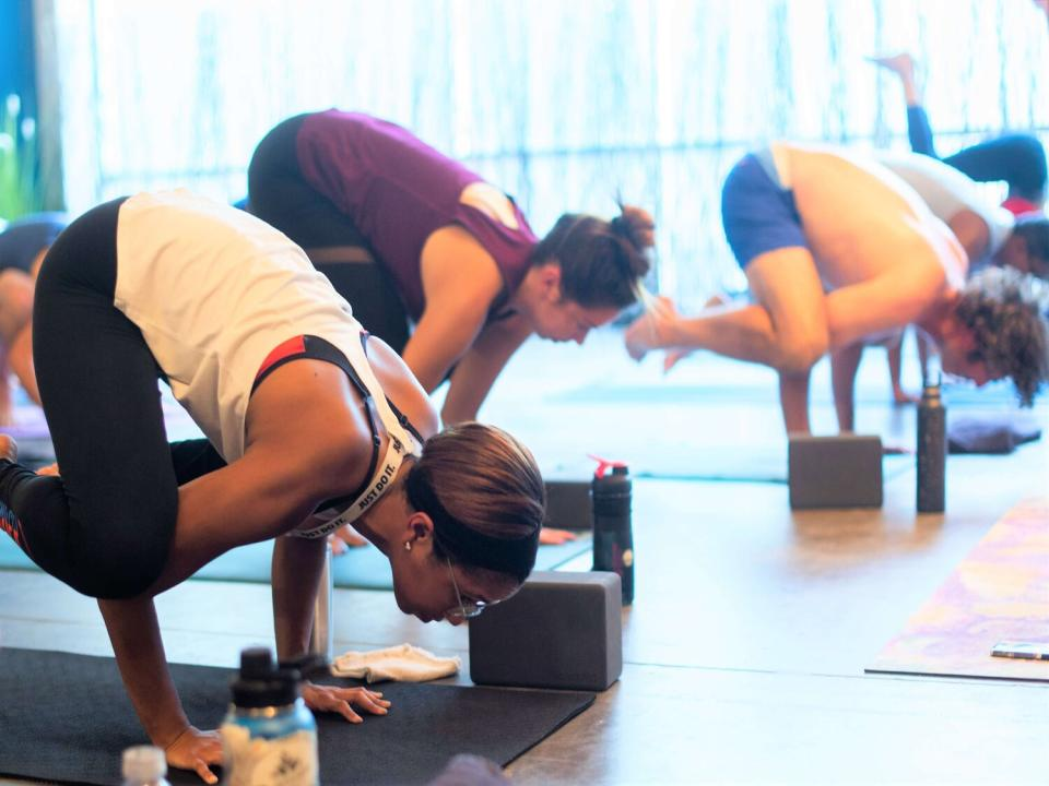 students in a yoga teacher training doing crane poses